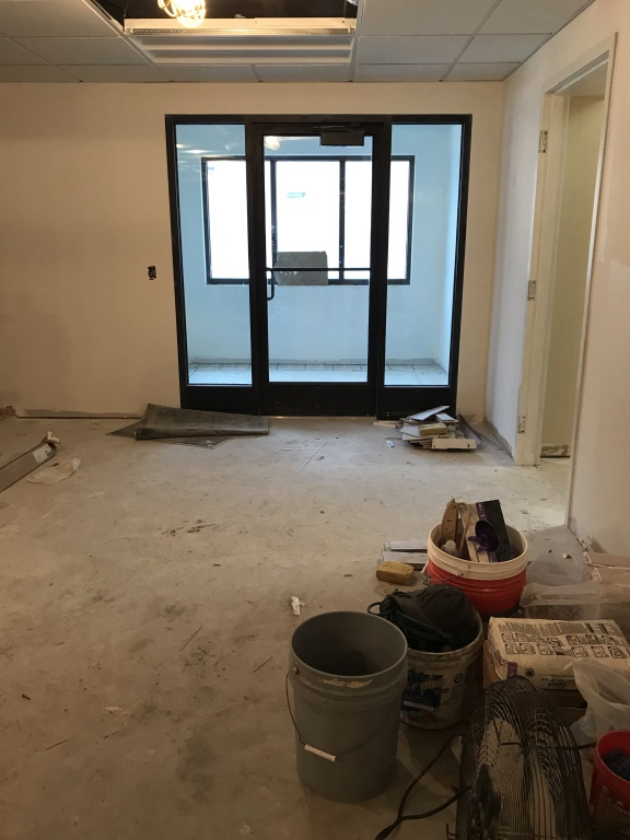 New entry door; light paint color on the walls and construction material on the floor.