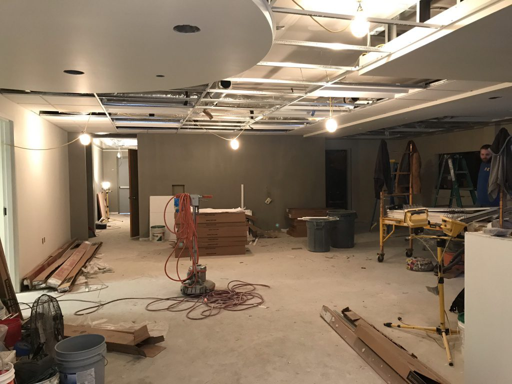 view of painted walls from new entry way of lobby, worker and construction materials.
