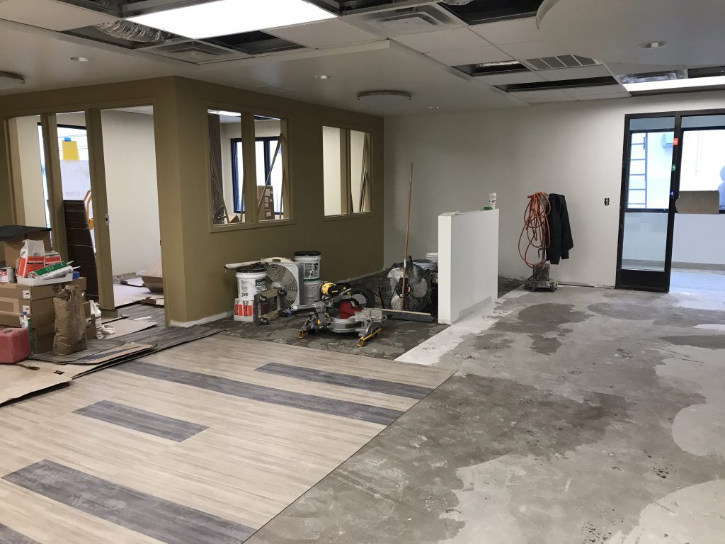 New waiting area with flooring being installed. New office painted with boxes of flooring.